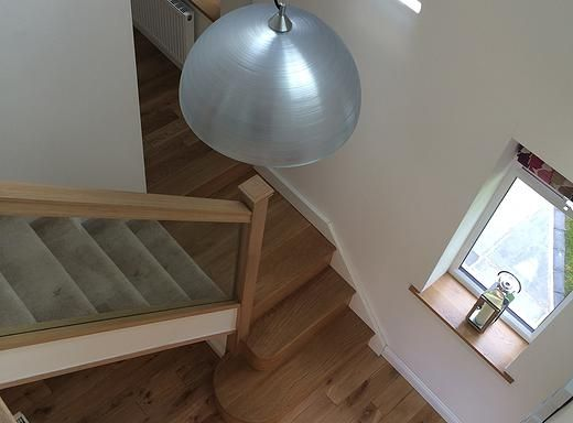 Residential Architecture. View down oak clad stairs with glass balustrade. Bungalow extension in Huddersfield by Bamford Architectural Ltd. Holmfirth.