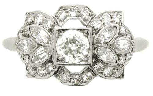 Diamond ring, American, circa 1950. A platinum and iridium ring set with one central round old cut diamond bead set in a millegrain box collet (approx 0.40 cts), surrounded by a horizontal openwork geometric bezel set with six marquise shaped diamonds (approx  0.60 carats), and 28 round old cut diamonds in millegrain bead settings (approx 0.60 cts), on a tapered knife edge shank, and with an approximate combined diamond weight of 1.60 carats.    Berganza.