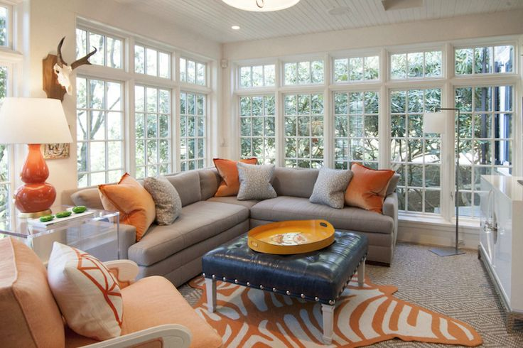 Gray and orange living room features walls of undressed windows lined with a gray sectional sofa adorned with gray and orange pillows facing a white lacquered media cabinet, Jonathan Adler Channing Buffet Table, topped with flatscreen TV across from a navy leather ottoman with silver nailhead trim topped with vintage Hermes tray atop an orange zebra rug, Jonathan Adler Zebra Peruvian Llama Flat Weave Rug, layered atop a diamond jute rug.