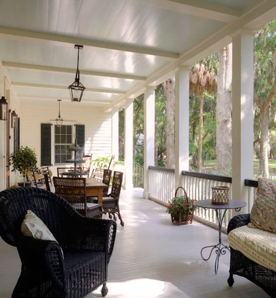 """Unforgettable Front Porches — Prime Perch (Glo.msn.com, photo courtesy of Houzz/Photo: John McManus/Design: Group 3) (""""This stately porch is attached to a house on balmy Daufuskie Island, S.C. The dark wicker furniture contrasts beautifully with the house's white walls and black shutters, and the porch is so spacious a full-size dining table and chairs fit easily. The porch is lit by Bevelo's French Quarter, and the ceiling paint is Benjamin Moore's Sage Tint."""")"""