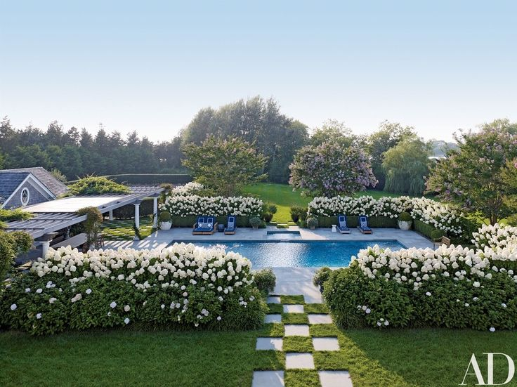 Enhancements made by Juan Montoya Design to a family home in Southampton, New York, include a pergola-topped dining space the firm added to the pool area. The chaise longues, by John Hutton for Sutherland, are cushioned in a Perennials fabric | archdigest.com
