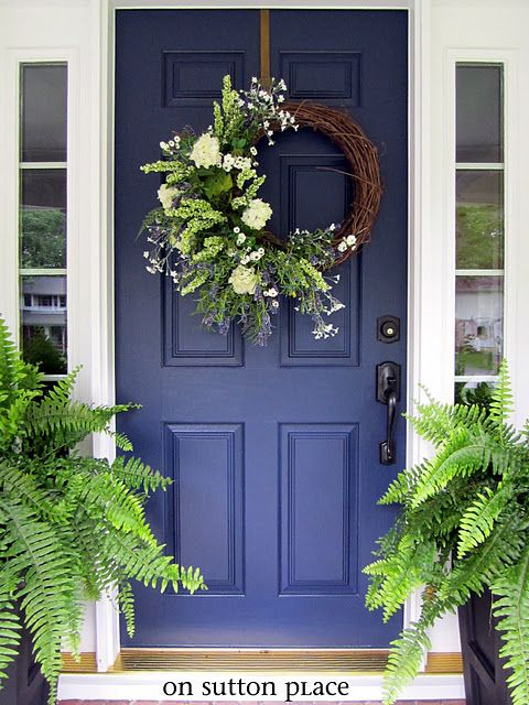 I love the blue painted front door.  I love the ferns flanking it, too.