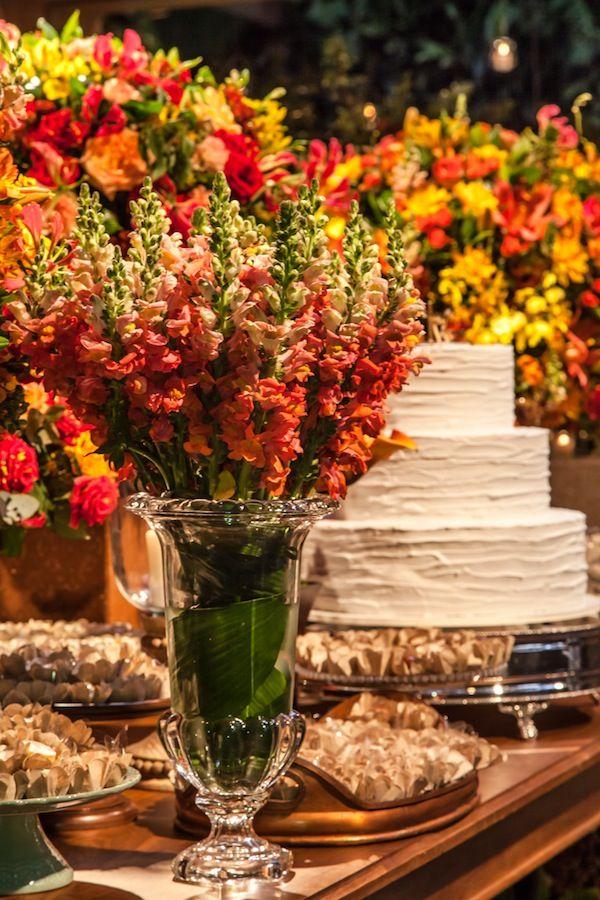 Mesa de doces em madeira com arranjos em tons quentes: vermelho, amarelo, laranja.... Decoração por Mariana Bassi Fotos : Helson Gomes