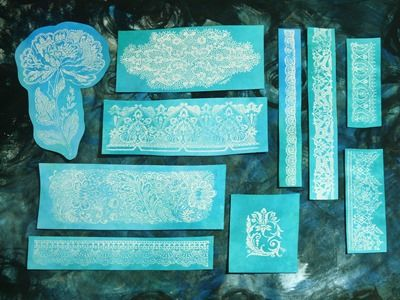 Embossed lace shapes made from stamped lace images with white embossing powder over inked background.