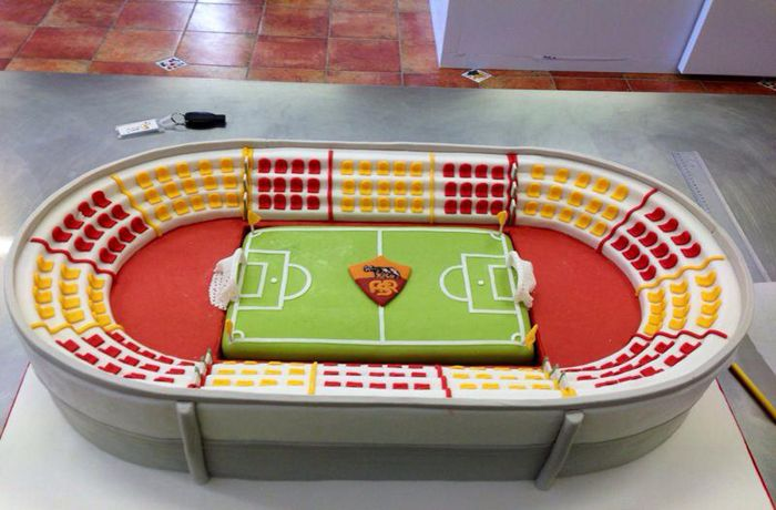 Festa a tema calcio con torta a forma di stadio.