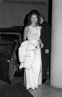 Jackie Kennedy arriving at a formal function with a white fur coat over her arm. September 27, 1966