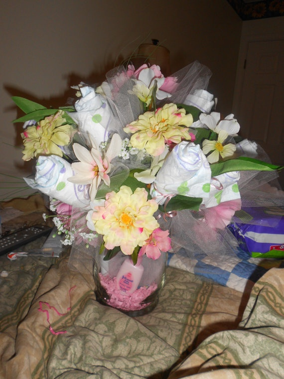 This is a handcrafted Floral Diaper Arrangement.  Made with lots of Love, size 1 diapers, this is the perfect gift for any new mom in the hospital.   Colors are pinks, yellows, and soft ivory...with lots of silk flowers that will last a lifetime, included also in the bottom of the vase is a 5 piece ...