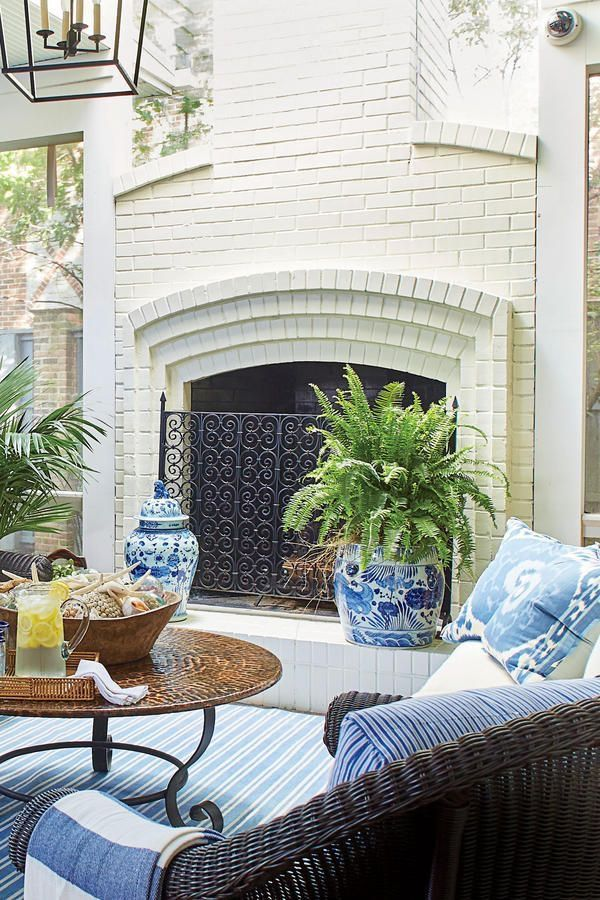 Blue and white ginger jars, white outdoor fireplace with blue and white accessories balance wood tones