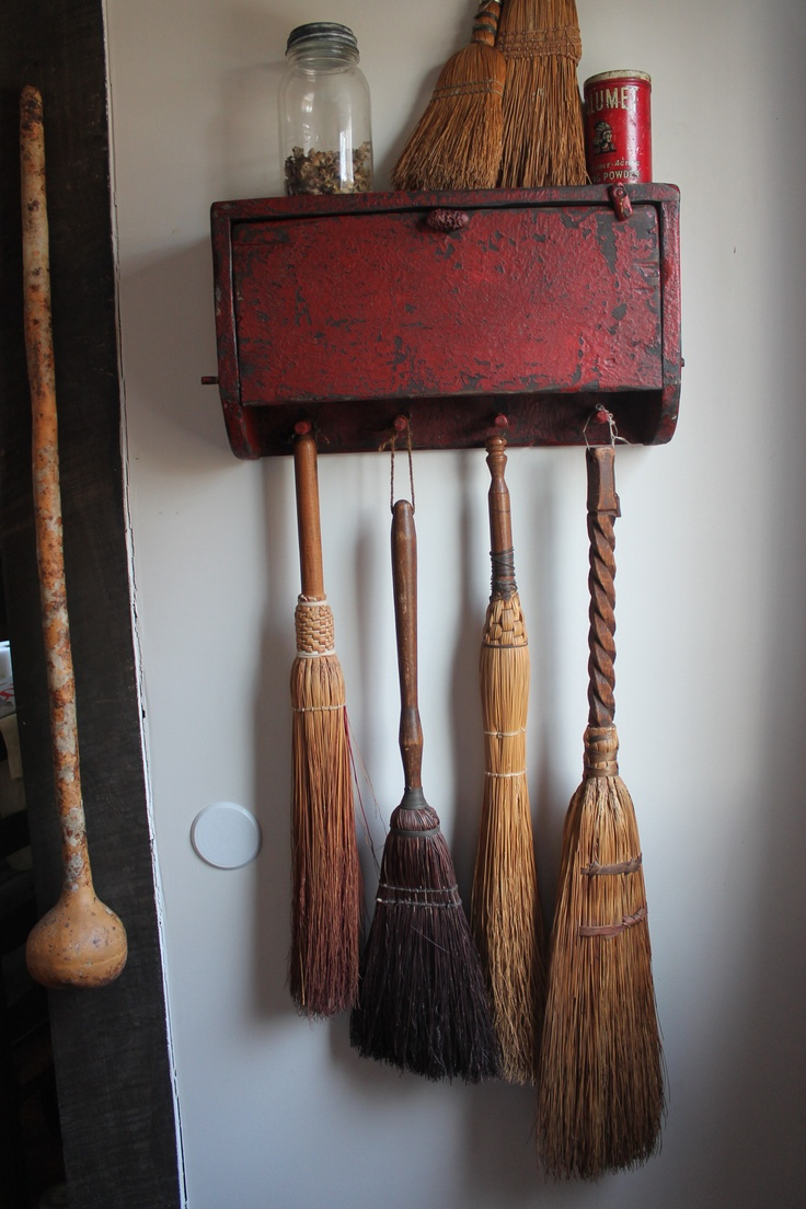 Old wood box wall hanger with broom collection.