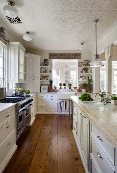 Farmhouse style kitchen with farm sink and white cabinets, linen skirt, tin ceiling, and wood floors by Giannetti Home and Brooke Giannetti. Home is a beach cottage in Santa Monica.