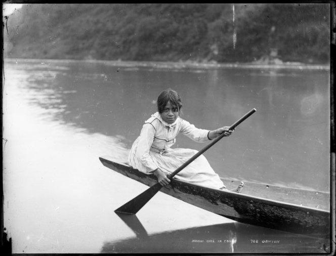 Maori girl in a waka, probably on Whanganui River