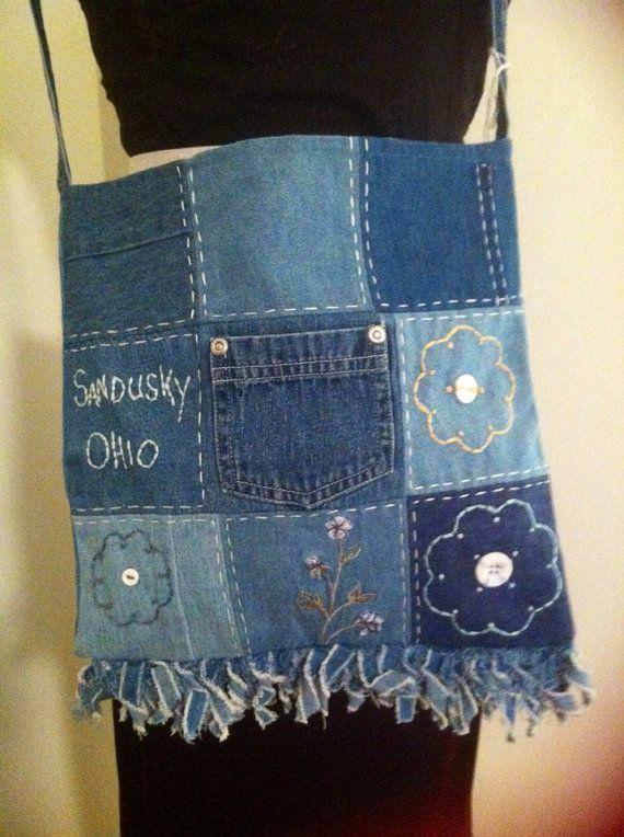 Chutes de jean bleu recyclé dans ce merveilleux sac très tendance. Ce sac mesure 11 X 11 pouces et est décoré avec des points de broderie à la main de fleurs et de lOhio de Sandusky nom (point de cèdre) il a des boutons colorés, une frange de jean bleu recyclé 2 pouces sur le fond, une sangle dépaule recyclé bleu jean 37 pouces et une doublure en coton bleu assorti. qualité de fabrication artisanale unique en son genre.