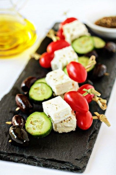 Greek style kabobs with black olives, cucumber, feta cheese and tomatoes served on a slate platter