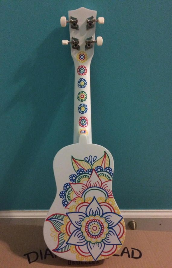 Painted Diamond Head ukulele. The back is covered in rainbow colors along with decorations on the front and neck. Comes with bag
