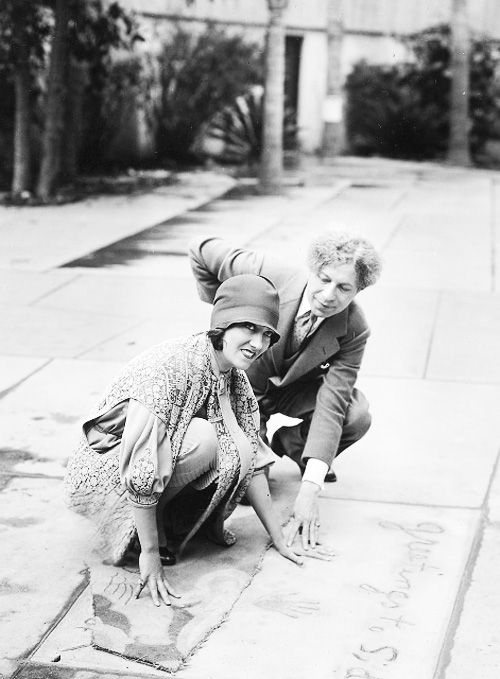 Gloria Swanson immortalizing her handprints with Sid Grauman helping in the forecourt of Grauman's Chinese Theatre. Gloria was one of the first stars to have contributed her prints, 1927