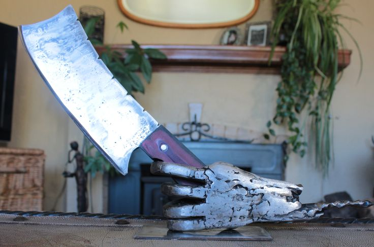This knife was made out of a leaf spring,the handle is micarta (not sure on the spelling).And the hand is made from scrap metal.