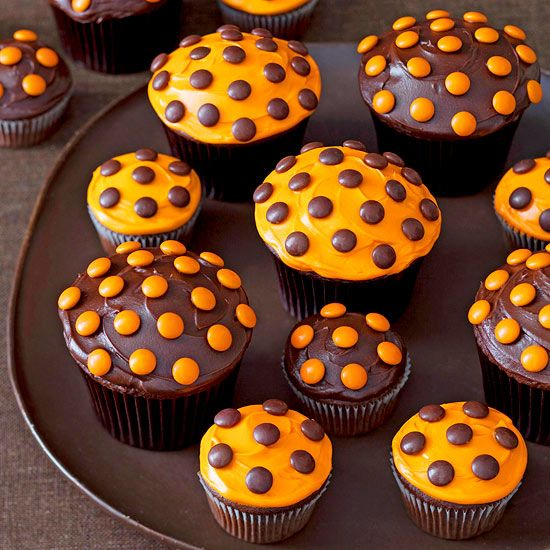 Top frosted cupcakes with chocolate candies for an easy-to-make Halloween dessert! See more ideas for spooky cupcakes: http://www.bhg.com/halloween/recipes/17-frightfully-good-halloween-cupcakes/?socsrc=bhgpin100212mmtoppedcupcakes#page=4