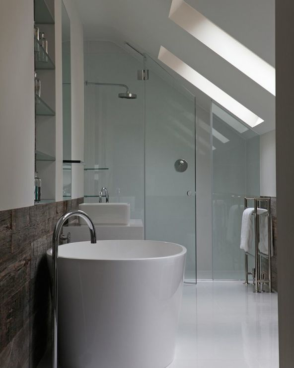 Fantastic bathroom boasts sloped ceilings accented with side-by-side skylights over freestanding towel warmer next to sloped, seamless glass shower with rain shower head.