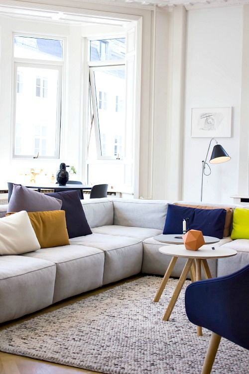 Ambiance décontractée et dans l'air du temps - un canapé et un tapis moelleux, des coussins colorés...
