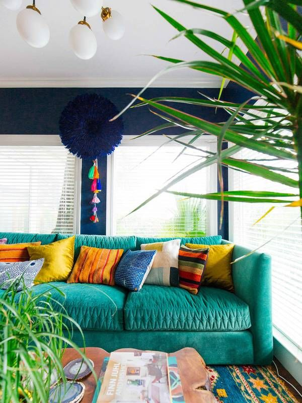 navy walls, teal couch, house plants, and bright pillows