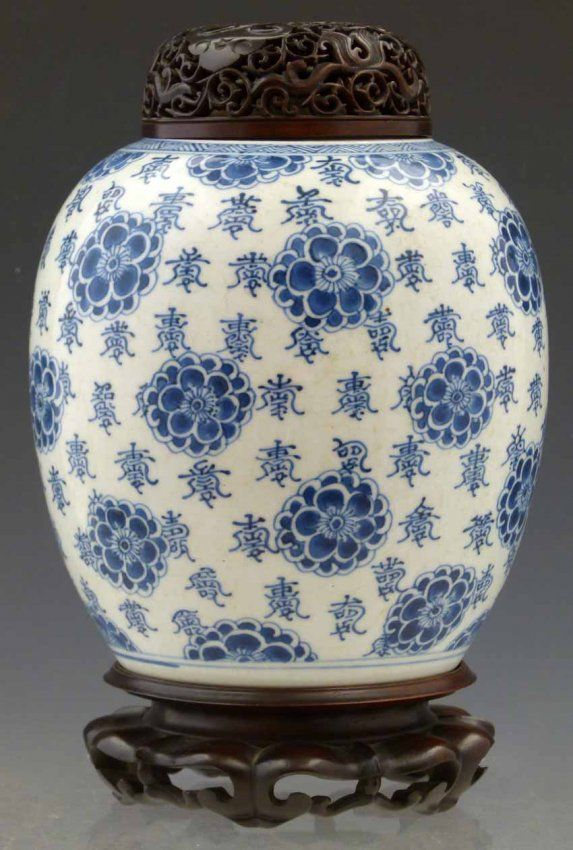 Chinese blue and white globular vase, Kangxi period, painted with florets and numerous instances of an auspicious character, double rings to base, height 19.5cm, together with a pierced hardwood cover and carved stand.