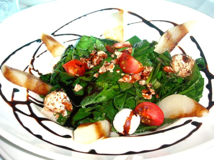Una ensalada de espinaca con bolitas de queso de cabra, nuez garapiñada, pera y una vinagreta de reducción balsámica.