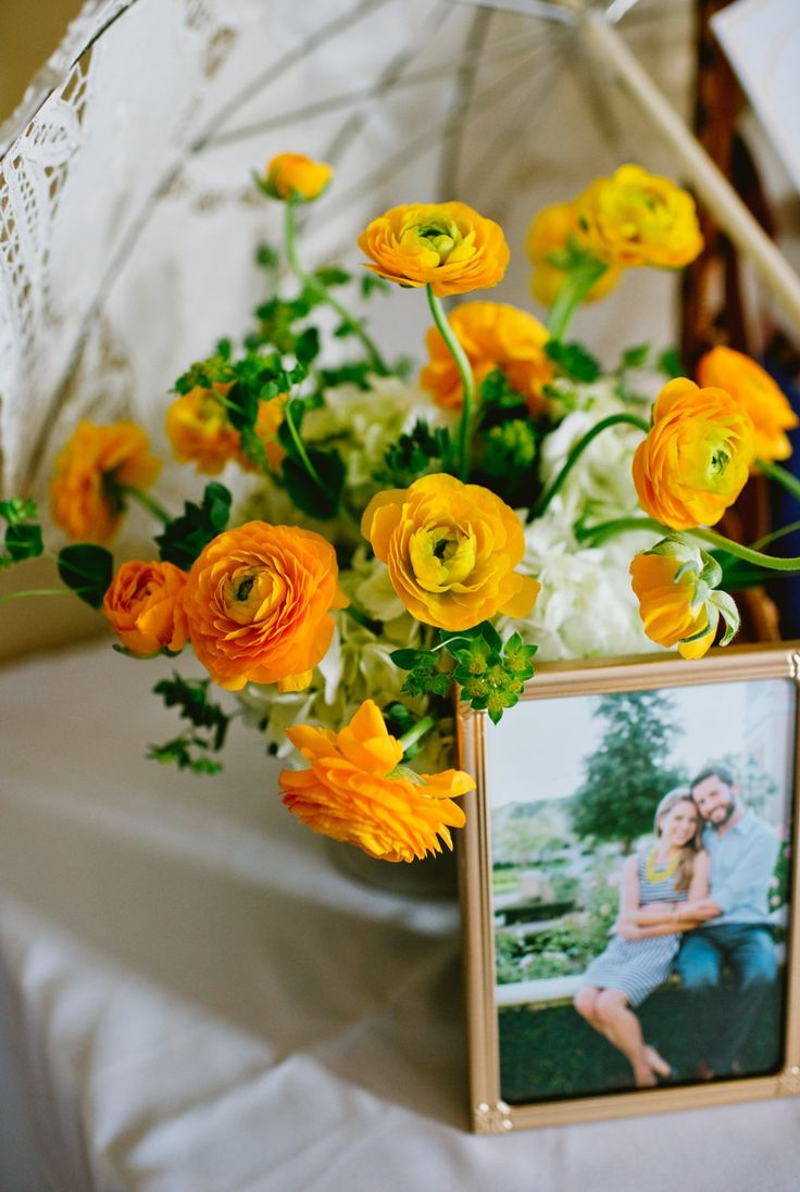 table centerpiece is made up of yellow ranunculus and white hydrangea