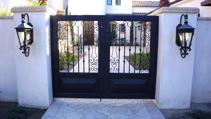 Accompanied by light fixtures, an all-custom, wrought iron, double entry gate was added to this Spanish style home.