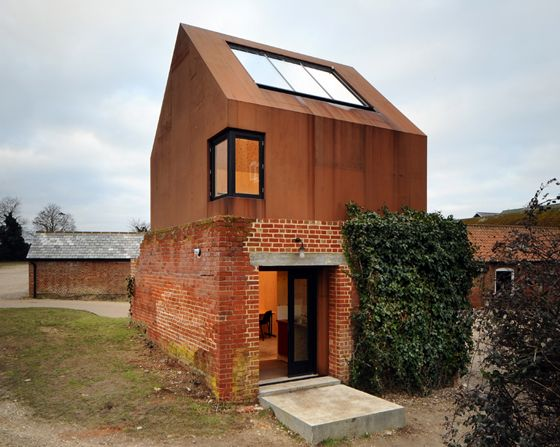 The rusted hue of the Cor-Ten steel in Haworth Tompkins Architects's Dovecote Studio project is similar to that of the red brick farm buildings nearby; photo: Philip Vile