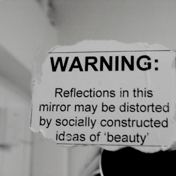 """Warning: Reflections in this mirror may be distorted by """"socially constructed ideas of beauty."""""""
