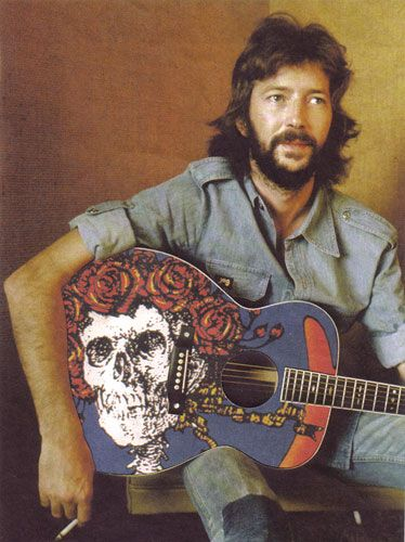 Eric Clapton with a Grateful Dead skull and roses guitar.http://www.usedinstrumentsmichigan.com/