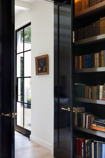 Hand scraped limed oak floors and celebrated hardware give warmth to the interiors. In the library, black doors create a sophisticated contrast with the white of the walls for a crisp, clean feel.