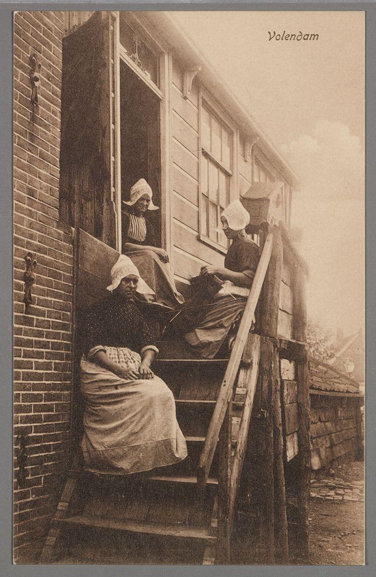 Drie vrouwen in dracht poseren op de trap en in de deuropening van hun woning. De rechter is aan het breien. 1905-1915 #NoordHolland #Volendam