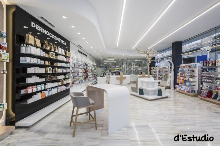 Inside the pharmacy, ceiling lights guide the client to the counters while sales areas are arranged on the back wall and around a bespoke wooden piece that holds a dry tree above the client.