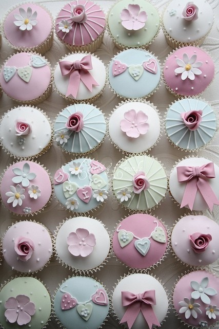 Set of pale green, blue, and pink cupcakes topped with flowers, bows, and mini garlands of hearts spelling out words. Vintage look. Originally done by Cotton & Crumbs Bakery for a christening but could work in almost any setting. om-nom-nom