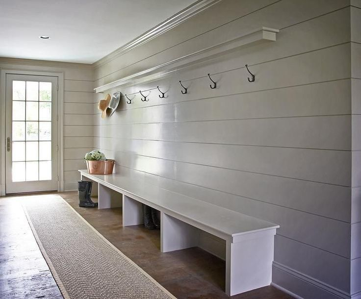 Gray mudroom boasts gray shiplap walls lined with a shelf ledge and a row of hooks over an extra long bench alongside a bound herringbone sisal runner.