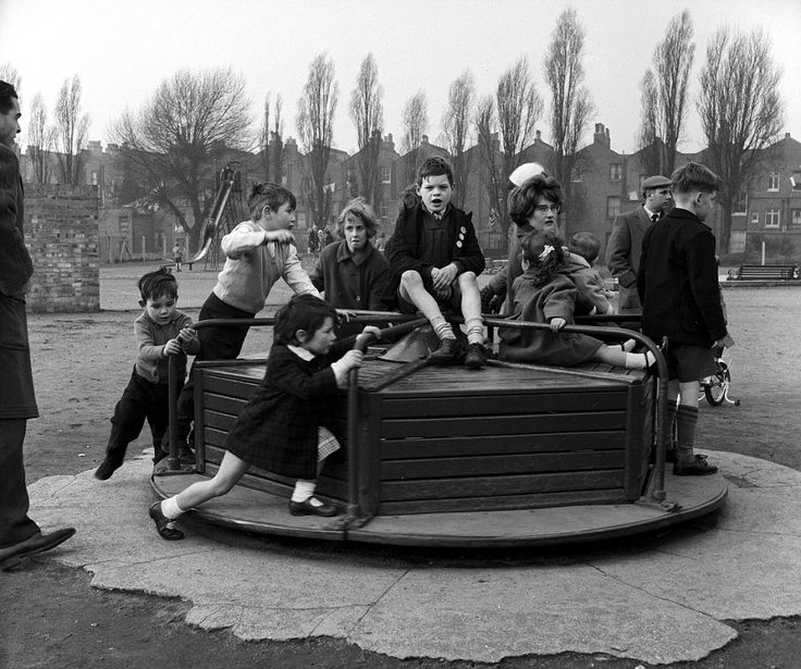 In for a spin: Toddlers from the early Fifties giving the roundabout a hefty push to make it go faster