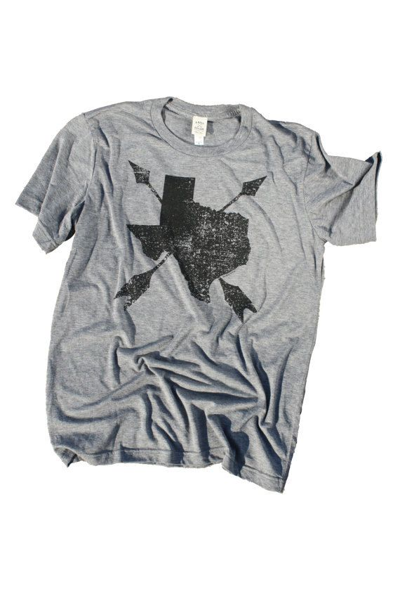 Texas shirt. Texas Graphic Tee. Arrows on Texas State t-shirt - Black ink on grey heather. Size MEDIUM.  Super soft Texas Friendship Tee. Crossed arrows pointing up - the Native American symbol for friendship. A must have for any genuine Texan. Proudly printed in distressed black ink on heather grey. An original design by our company, A Rosy Outlook Designs, Inc., based just outside the Music Capital of the World, Austin, Texas!  This listing is for size MEDIUM, UNISEX. 50% poly 25% combed…