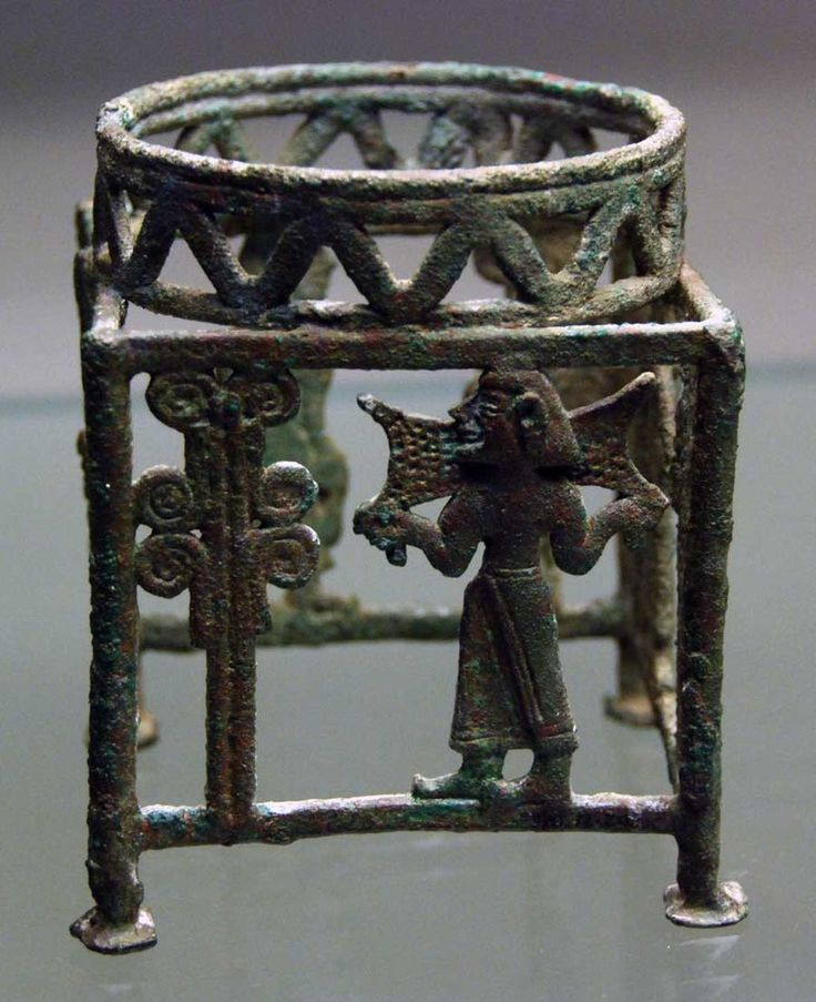 Cyprus bronze coiled wire ceremonial stand, possibly Kourion, Cyprus, 13th-12th century B.C.  Shows a man carrying an oxhide ingot towards a tree, and another playing a lyre, hints at close relationship betwen copper production and elite ritual on Cyprus. British Museum