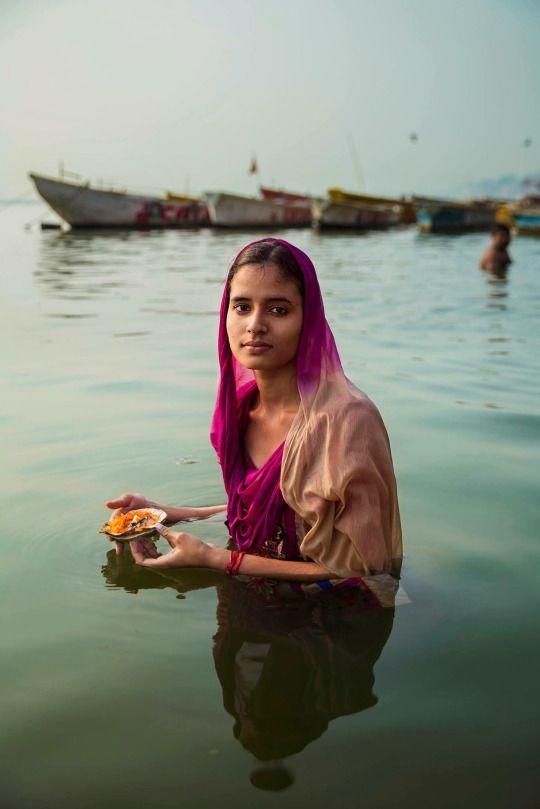 Hindu pilgrim making an offering on the Ganges river. In Varanasi, India.