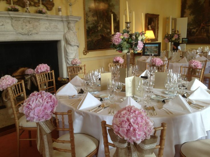 Top table chairs decorated with pink hydrangea with natural ribbon.