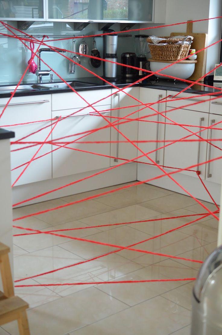 Für Spiel Nr. 3 hatte ich meine Küche in ein Laserfeld verwandelt. Es war der einzige Raum in dem das Spannen der Schnüre so möglich war! Wir haben kaum Wände im Haus!  Die Kinder mussten nun alle einzeln durch dieses Laserfeld zum Waschbecken durchkämpfen, ein Glas mit Wasser befüllen ans andere Ende der Küche durchrobben und dort eine mit blauem Antigiftserum bereitstehende Karaffe mit ihrem Wasser befühlen! Ich sag nur: Zum Glück haben wir Fliesen in der Küche!