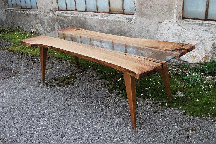 Tavolo realizzato dalla combinazione di due tavole in legno di noce nazionale centenario unite da una lastra in vetro extrachiaro. Il basamento in ferro è stato verniciato a mano di colore oro.