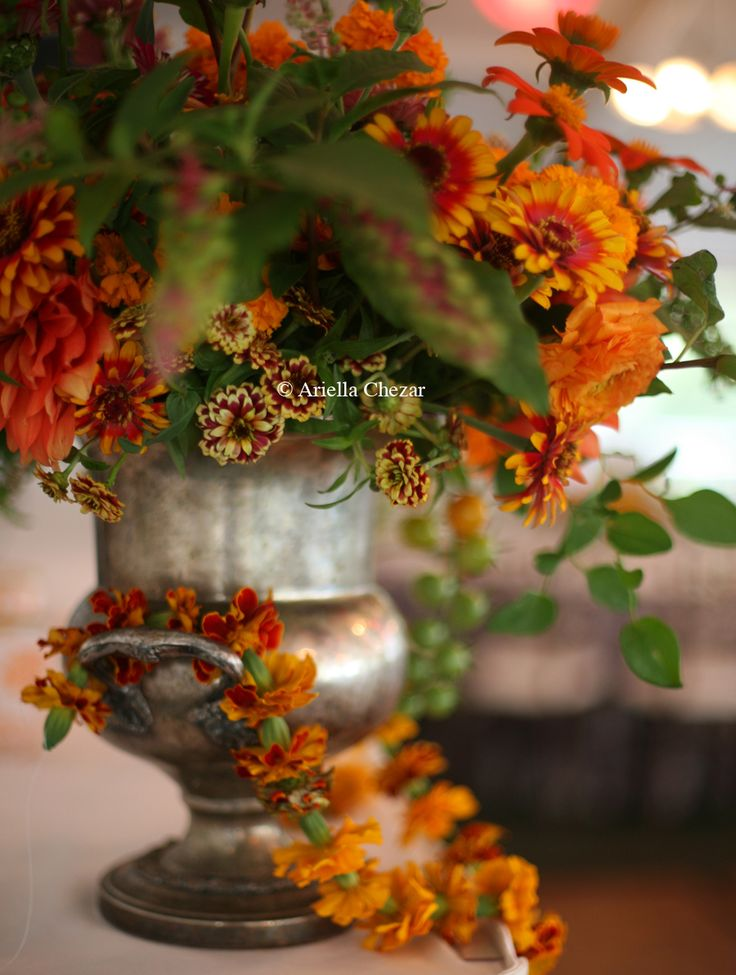 A vintage ice bucket is transformed into a stunning vase for fall foliage and seasonal flowers.
