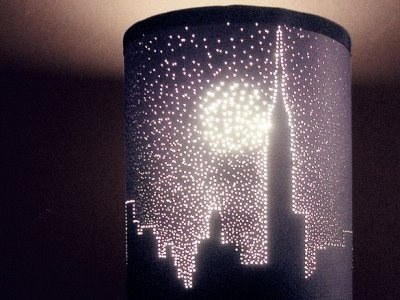 black construction paper, a needle, and a light! you can put this over a nightlight or an old ugly lamp! even better, you can decorate the base of the lamp with sharpie and put it in the oven for an hour to set it and voila, you have a beautiful diy lamp