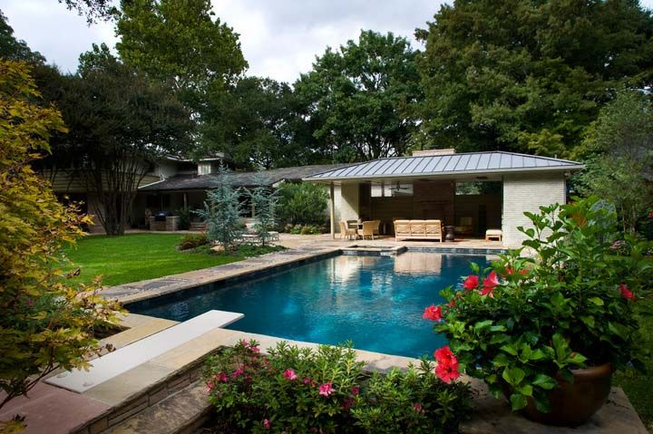 modern rectangular pool with diving board and modern pool house