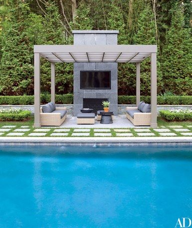 In a Westchester County, New York, home by Vicente Wolf, the chairs' seat cushions are made of an Edelman leather, and the bespoke banquette is covered in a Stark fabric. The poolside pergola features a Samsung outdoor television, sofas and ottomans by Crate and Barrel, and Pottery Barn tables   archdigest.com