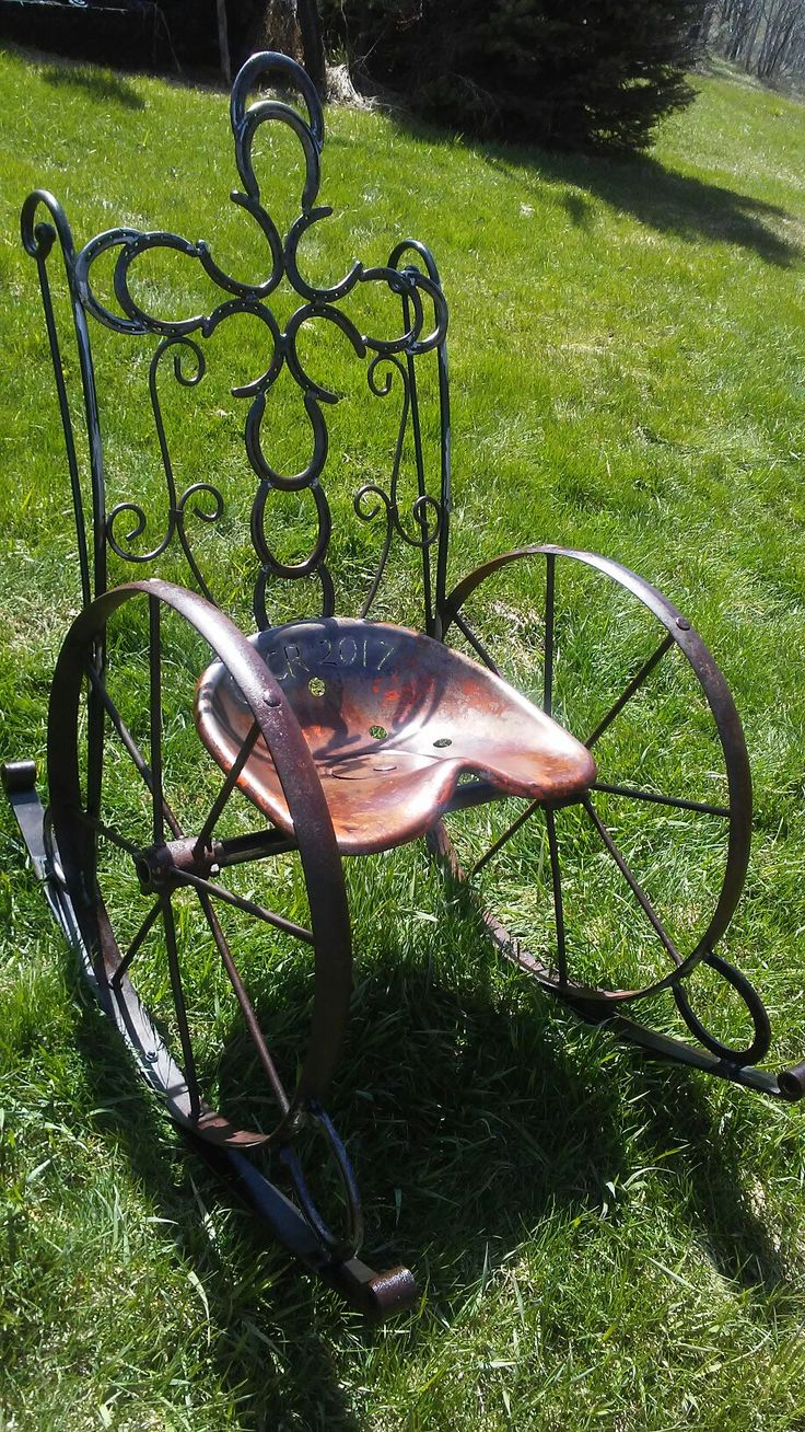 DIY metal rocking chair, made from a tractor seat, antique wheels, horseshoes, ornate scrolls, and springs.