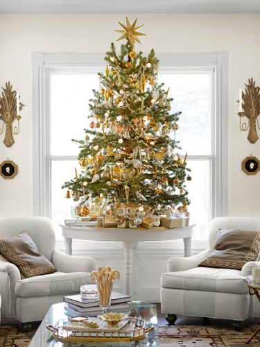 Great idea: Instead of one huge Christmas tree, decorate a few small ones, like this gold table-top tree