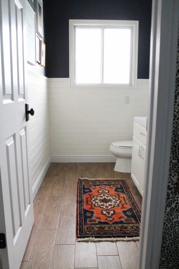 "(black?) window, white plank wainscoting with deep navy paint, ORB doorknob with backplate, gallery wall, oriental/kilim rug, ""wood"" floor"